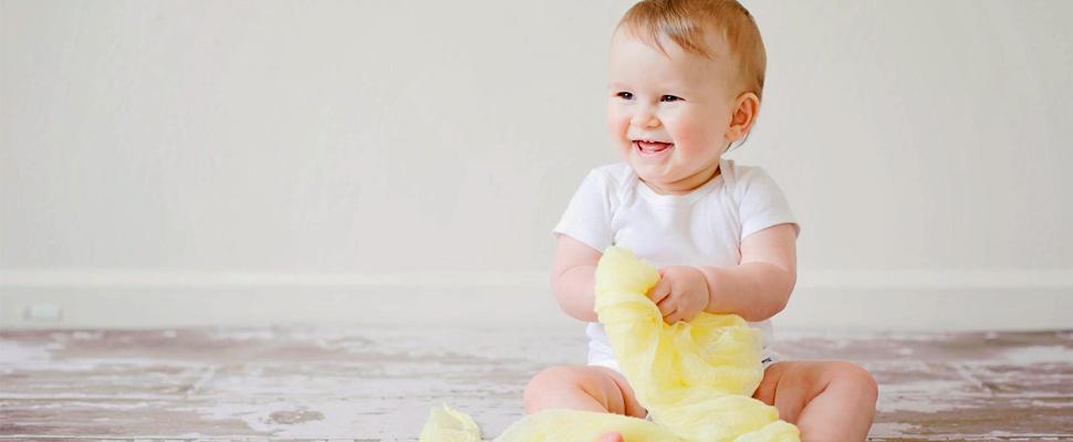 Bebé sentado en el piso jugando.