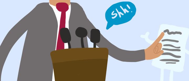 Político usando un traje con corbata roja - mesa con micrófonos