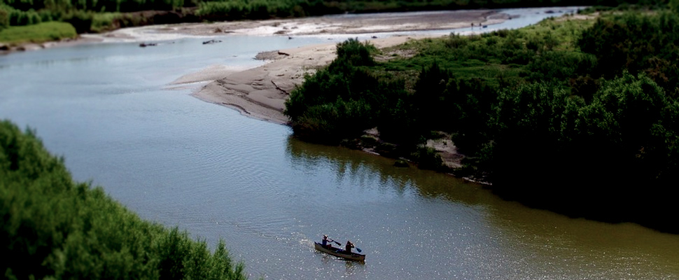 Canoe with two people sailing on the Rio Grande between the southern United States and northern Mexico