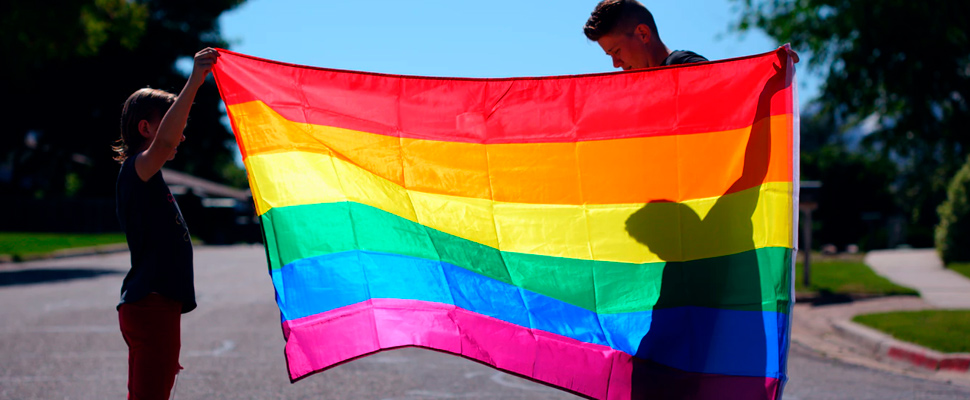 A parent and child holding a rainbow pride flag.