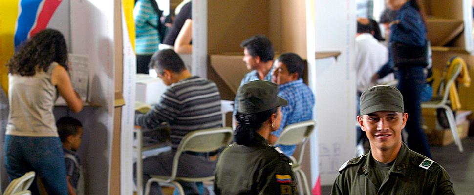 Policías colombianos supervisando las urnas mientras se realiza una jornada electoral.