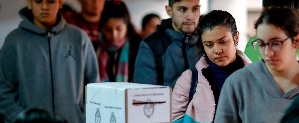 Personas hacen fila para efectuar su voto este domingo en Buenos Aires (Argentina).
