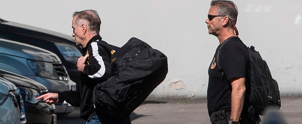 Businessman Eike Batista (L) is escorted by a police officer into the Federal Police headquarters after being arrested