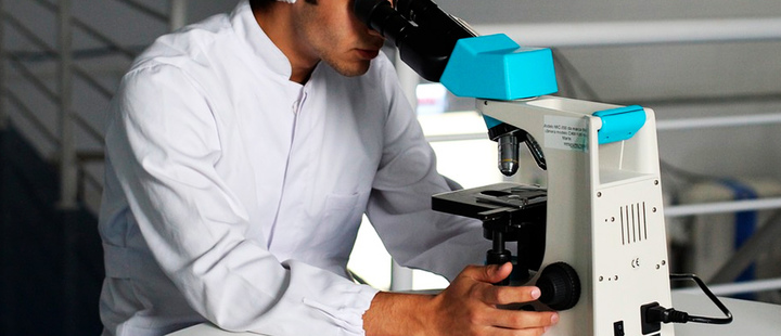 Scientist looking through a microscope in a laboratory.