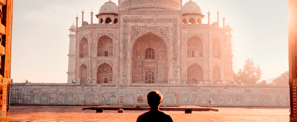 Silhouette of a person sitting in front of the Taj Mahal in India