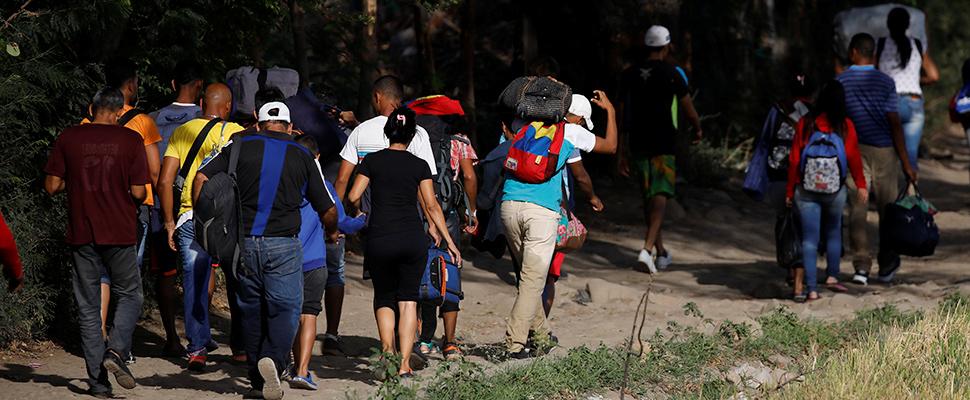 Venezolanos llevan sus pertenencias por un camino ilegal después de ingresar ilegalmente a Colombia