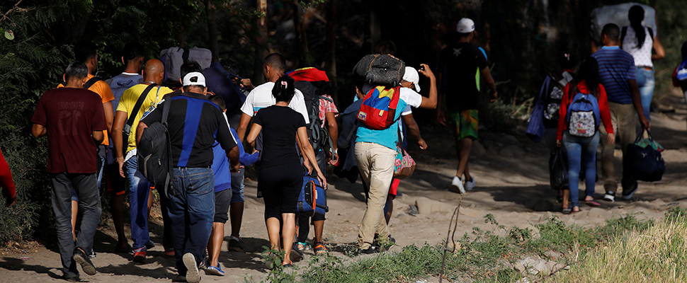 Venezuelans take their belongings on an illegal road after entering Colombia illegally