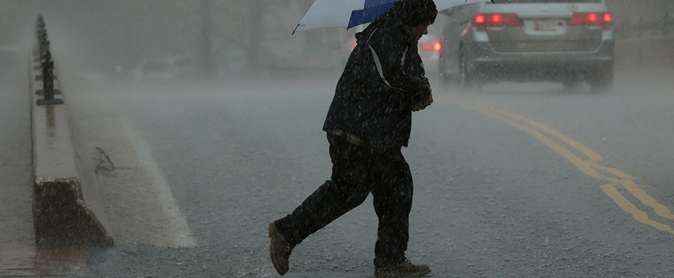 A man walks in a torrential downpour in Ellicott City, Maryland April 30, 2014.