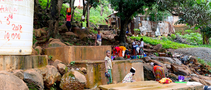 Women wash clothes in a stream in Freetown, Sierra Leone