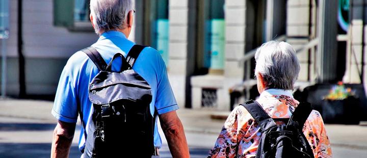 Two elderly people walking holding hands