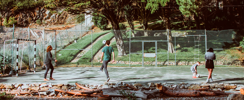 Four person playing ball surrounded by trees.