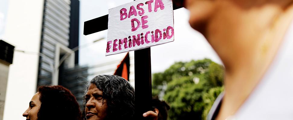 Una mujer sostiene un cartel que dice