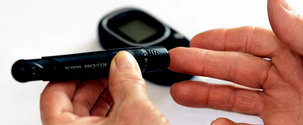 Person checking blood sugar level with glucometer