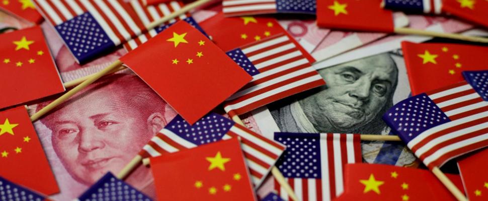 Billete de dólar estadounidense y un billete de yuan chino se ven entre las banderas de Estados Unidos y China