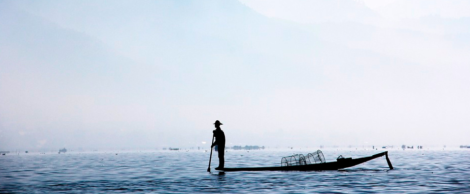 Pescador en una lancha en medio de un lago