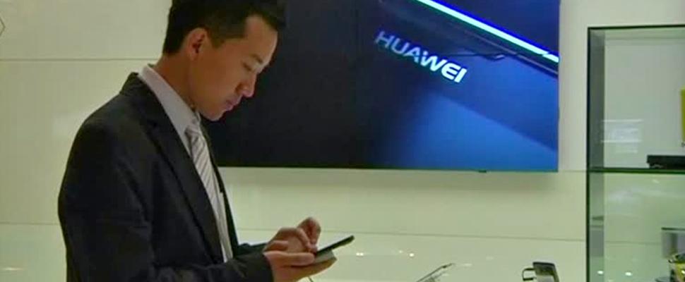Hombre de pie en la sala de Huawei usando un teléfono celular.