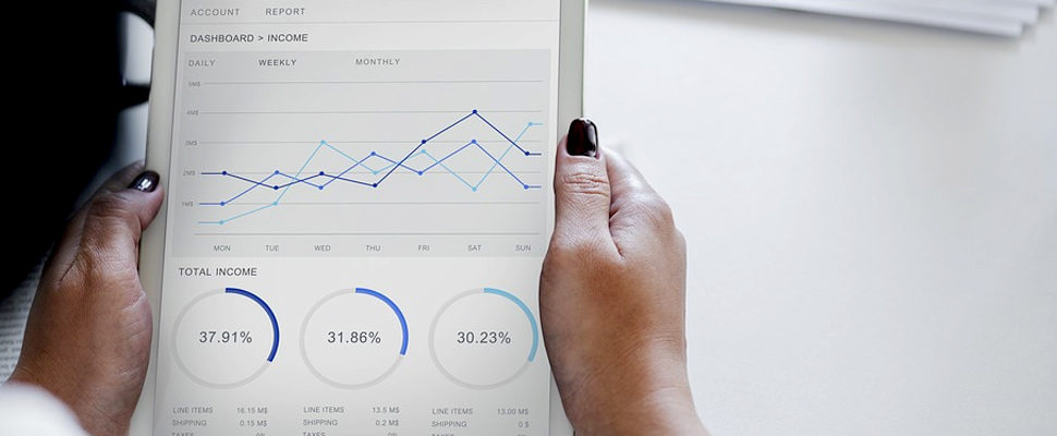 Woman holding a tablet showing statistics.