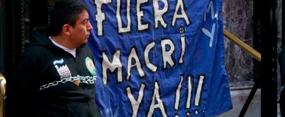 Manifestante al lado de una pancarta que dice