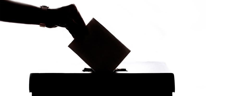 Mujer introduciendo su voto en una urna.