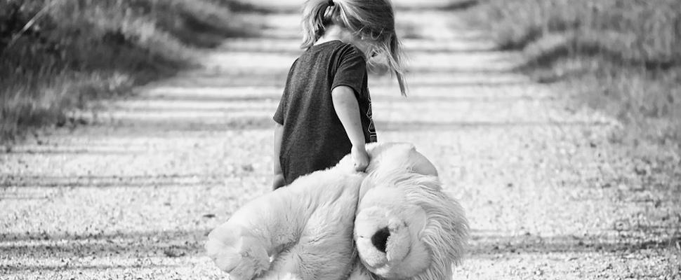 Girl walking on a road carrying a teddy bear.