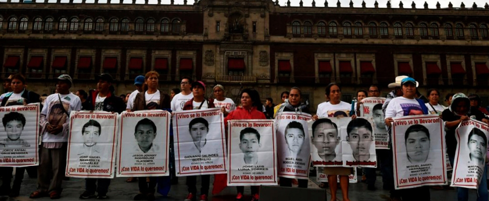 Familiares de los 43 estudiantes desaparecidos en Ayotzinapa, sostienen carteles con sus fotografías.