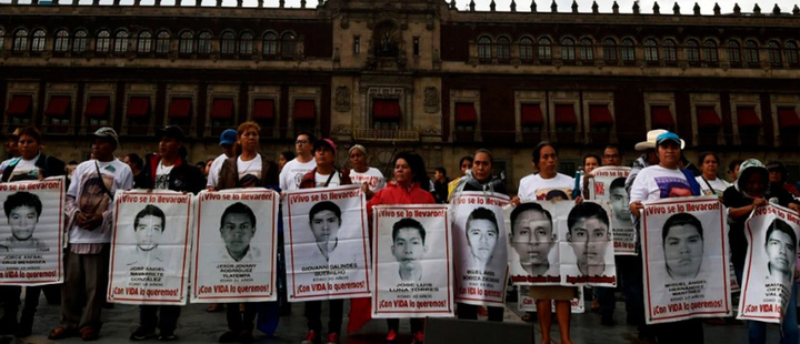 Relatives of the 43 missing students in Ayotzinapa, hold posters with their photographs.