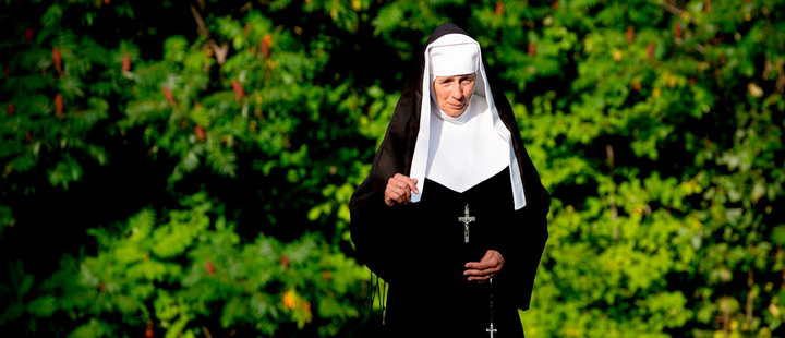 Nun walking near trees.