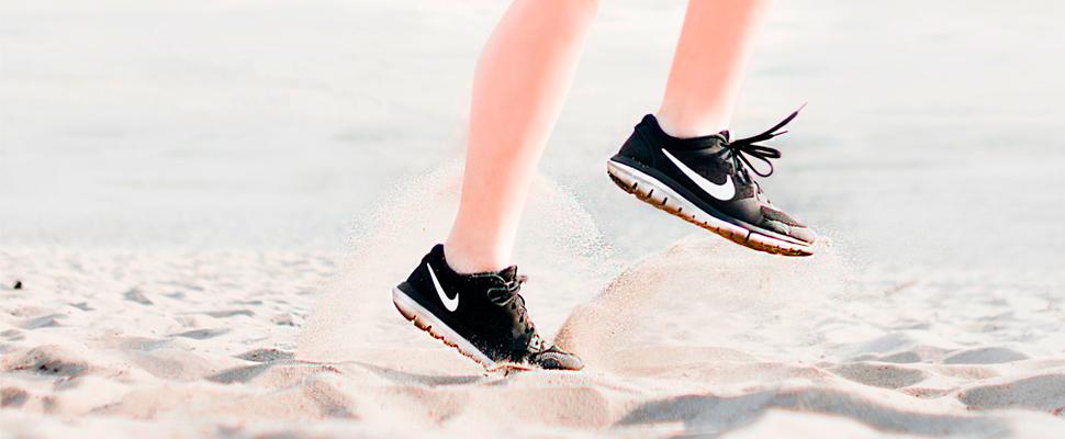 Woman wearing pair of black nike running shoes.