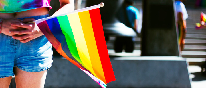 Woman holding a flag of the LGBTI + community
