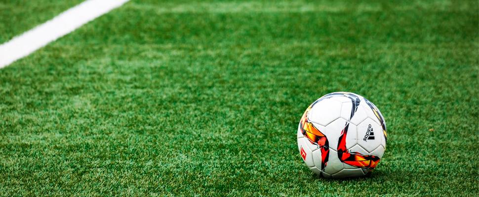 Balón de fútbol en un campo de gramilla.
