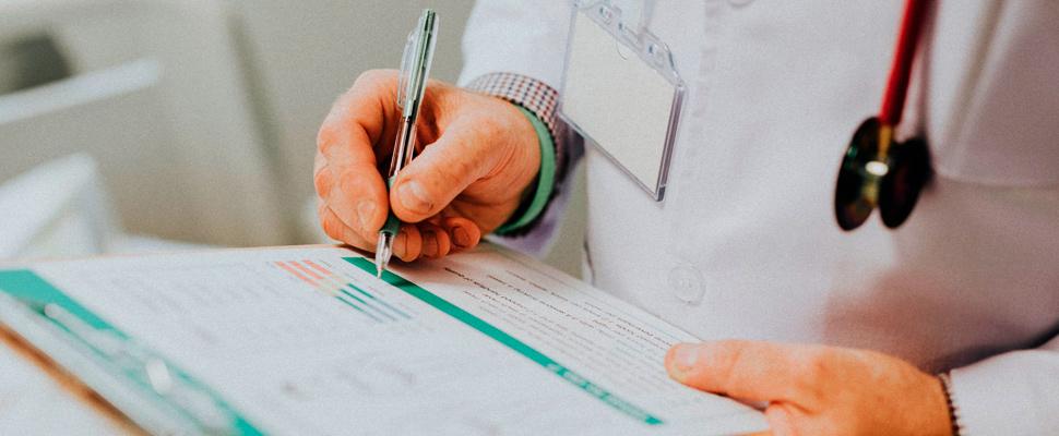 Doctor escribiendo informe médico