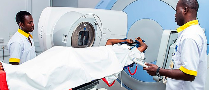 Ghanaian Radiotherapists treating a patient with a linear accelerator at the private cancer center in West Africa