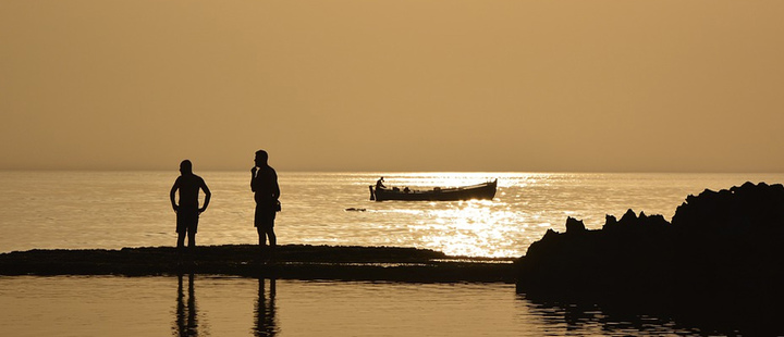 Two people near the sea and in the background a boat.