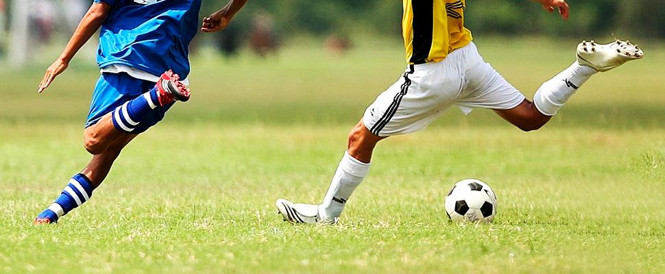 Dos jóvenes jugando fútbol.