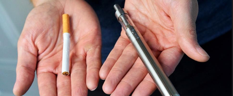 Persona sosteniendo en sus manos un cigarrillo normal y otro electrónico.