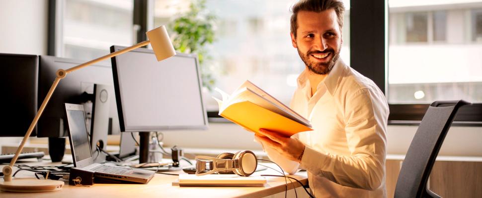 Hombre en una oficina sosteniendo un libro.