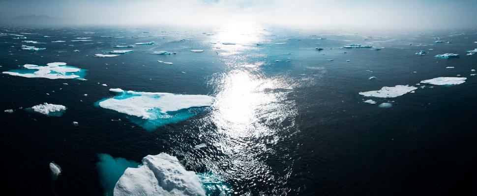 Paisaje y fotografía aérea de icebergs en el cuerpo de agua durante el día.