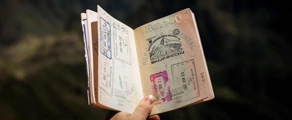 Hand holding an open passport.