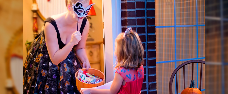 Woman delivering candy to a girl on Halloween.