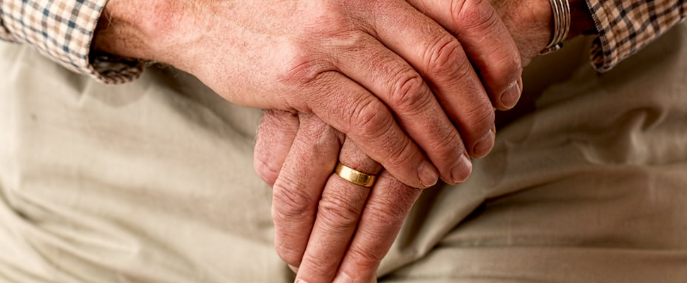 Hands of an elderly man on a cane