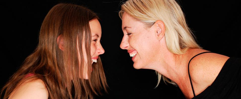Madre e hija sonriendo el uno al otro.