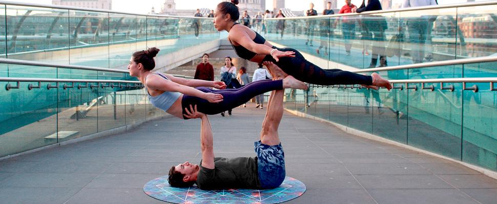 Hombre levantando a dos mujeres en medio practicando acrogym.