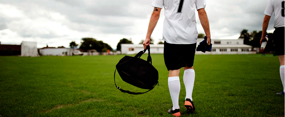 Footballer carrying a suitcase inside the playing field.