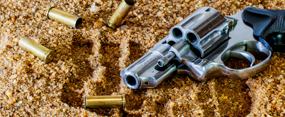 Stir lying on a surface with sand and bullets around.