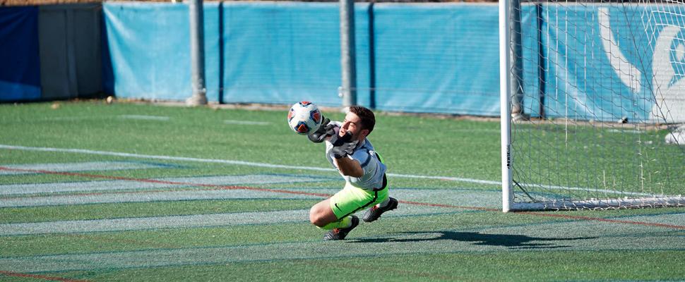 Portero atrapando un balón de fútbol.