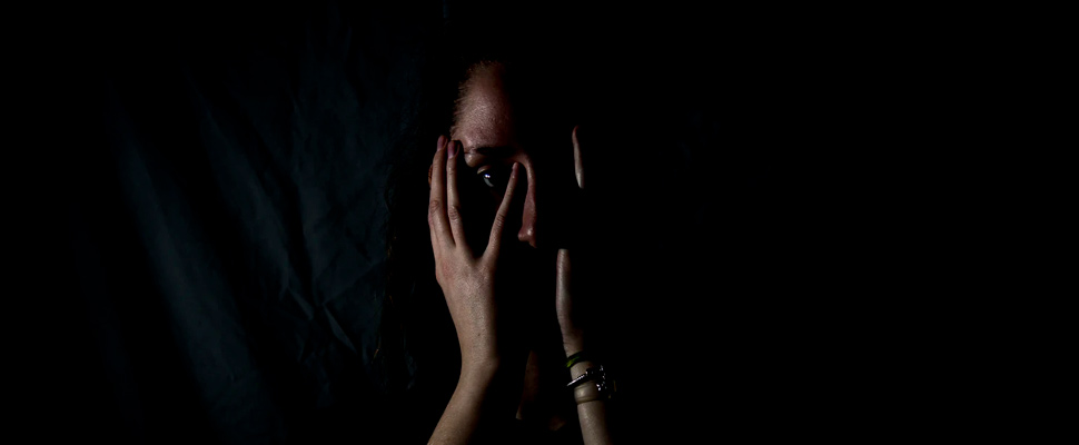 Woman holding her face in dark room.