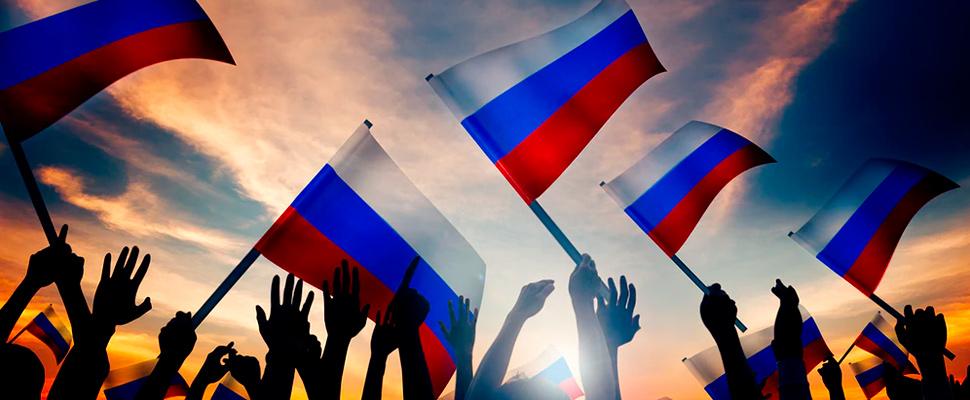 Grupo de personas que sostienen banderas de Rusia.