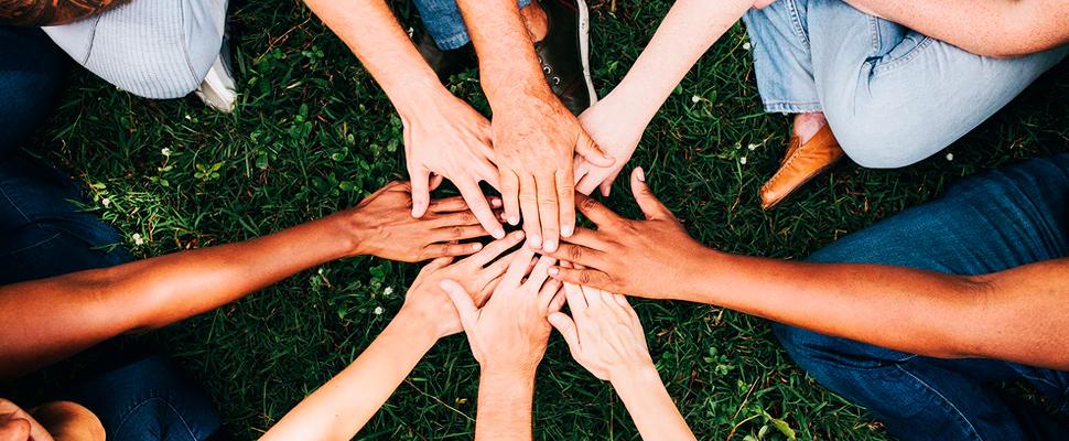 Grupo de personas juntando las manos.