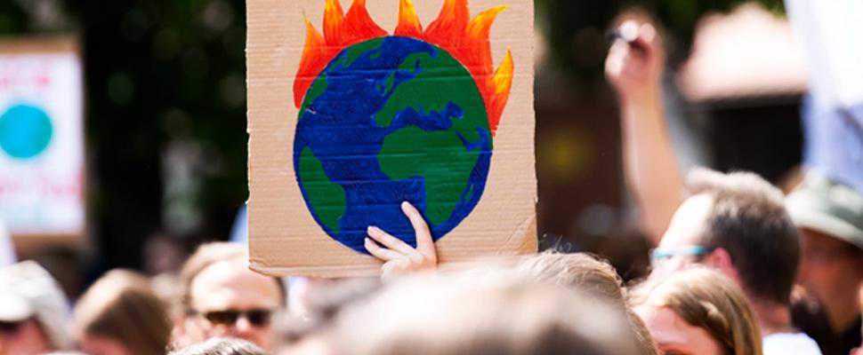 Persona sosteniedo un cartel en protesta sobre el cambio climático.