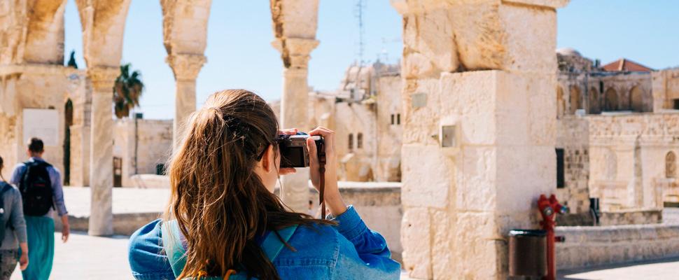 Mujer tomando fotos de las ruinas.